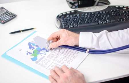 analysed: Economic document analysed with a stethoscope on a white desk