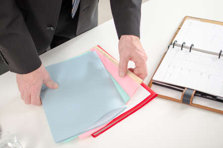 Businessman looking for documents on his desk photo
