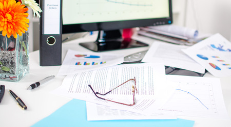 Desk cluttered with business documents