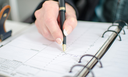 noting: Businesswoman in office noting an appointment in her diary, closeup