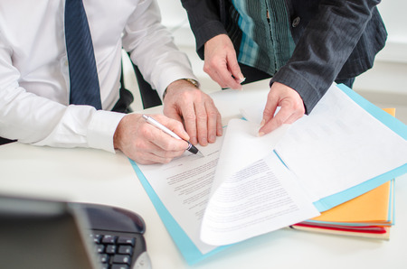 Businessman signing a documents presented by his secretary at the office