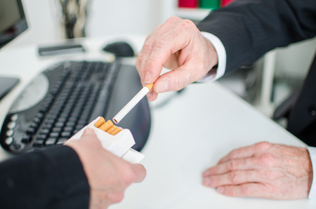 taking risks: Businessman taking a cigarette at the office Stock Photo