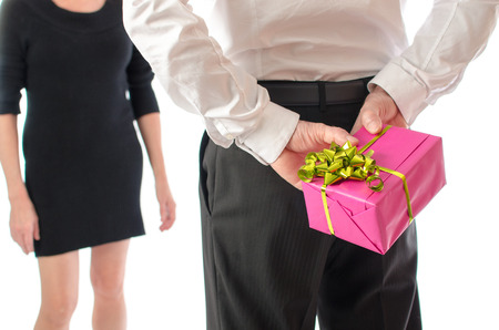 Man holding a gift behind his back in front of a woman photo