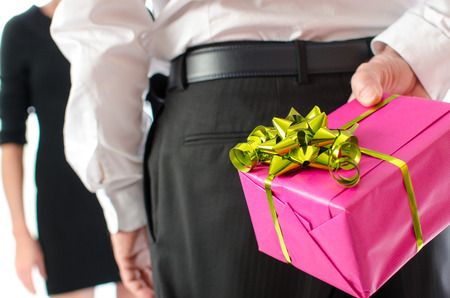 gift behind back: Man holding a gift behind his back in front of a woman Stock Photo