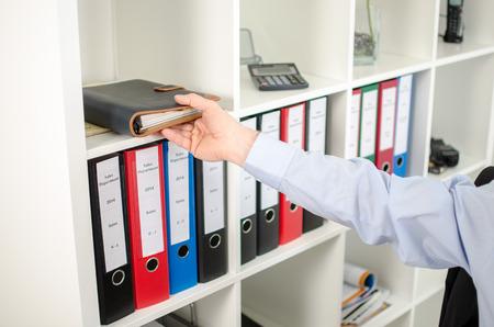 Geschäftsmann, der sein Tagebuch aus dem Regal im Büro Standard-Bild - 33070326