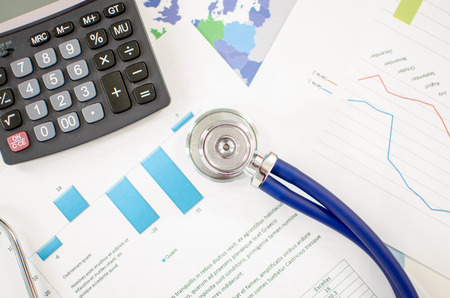 Stethoscope and calculator placed on financial charts photo