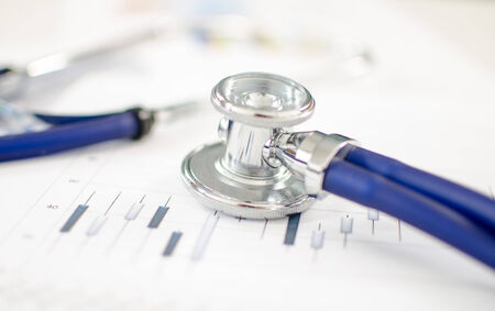Stethoscope placed on financial charts photo