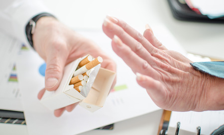 View of a womans hand refusing cigarette at office