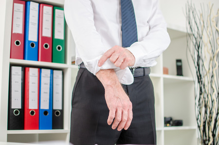 rolling up: Businessman rolling up his sleeves at office Stock Photo