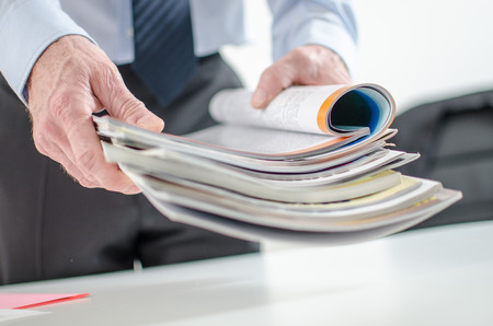Businessman holding magazines at office Stock Photo