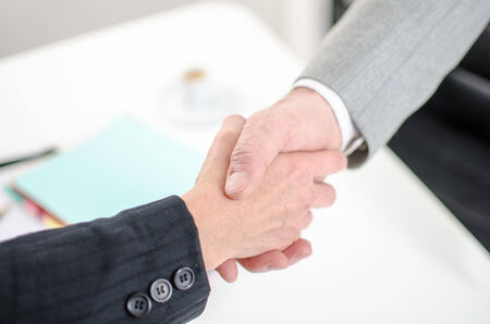 Business associates shaking hands at office, closeup photo