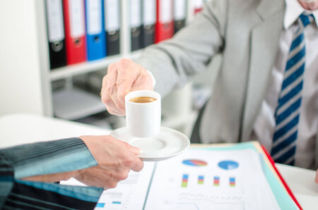 Assistant offering coffee to her boss at office photo