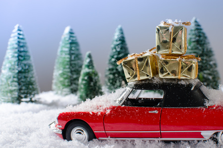 Red car with presents on the roof in a winter landscape photo