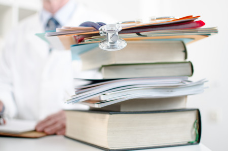 Stethoscope on a stack of medical books, closeup photo