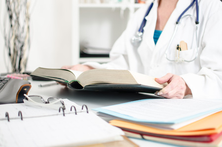 Female doctor reading a medical book at her desk Stok Fotoğraf