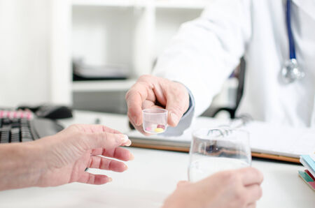 doctor giving glass: Doctor giving pills to his patient in his office