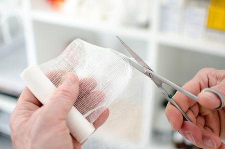 Doctor cutting a bandage, closeup