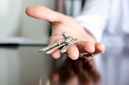 Inmobiliaria mostrando llaves de la casa en una mesa de madera Foto de archivo - 34423108