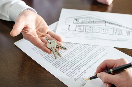 Realtor showing house keys and woman signing a real estate contract