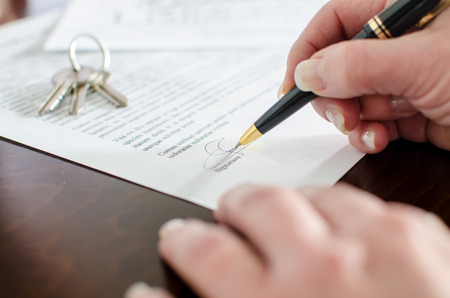 Woman signing a real estate contract, closeup