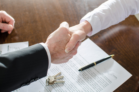 dandose la mano: Agente de ra�ces, agitando las manos con su cliente despu�s de la firma del contrato