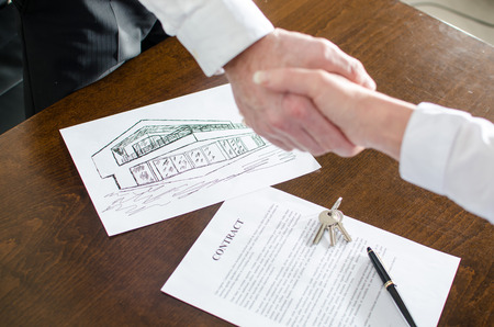 Estate agent shaking hands with his customer after contract signature photo