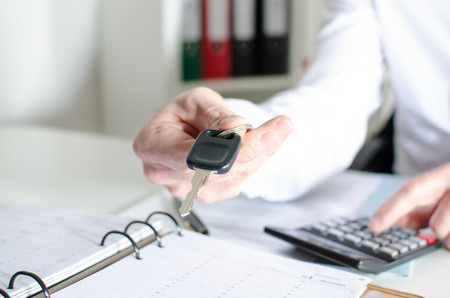 Car salesman holding a key and calculating a price at the dealership office Stok Fotoğraf