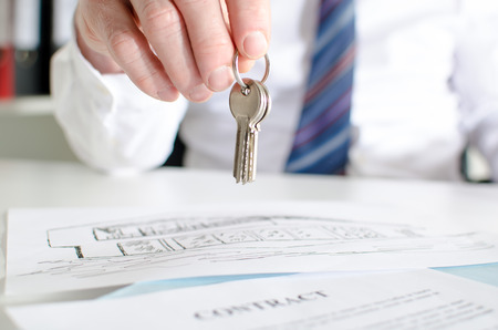 title: Estate agent holding house keys over a contract Stock Photo