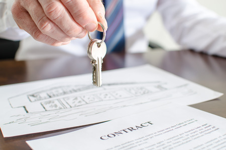 Estate agent holding house keys over a contract 스톡 콘텐츠