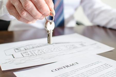Estate agent holding house keys over a contract Foto de archivo