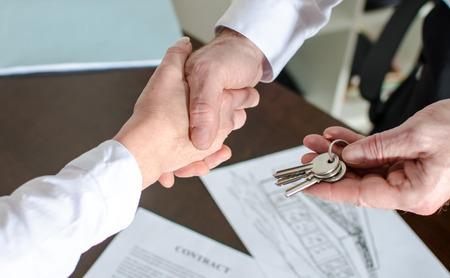 contratos: Agente inmobiliario que da claves de la casa al cliente despu�s de la firma del contrato Foto de archivo