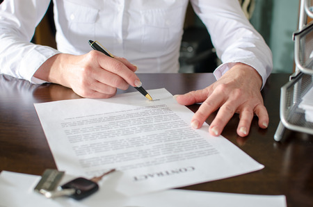 Woman signing a car purchase contract in car dealership