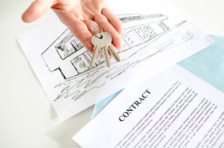 Realtor showing house keys over a contract Stok Fotoğraf