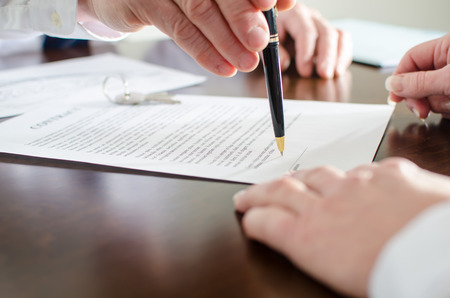 real estate contract: Realtor showing the signature place of a contract with his pen