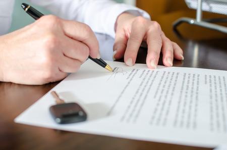 Vrouw ondertekening van een auto koopovereenkomst in autodealer