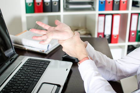 carpal tunnel syndrome: Businesswoman holding her painful wrist at office