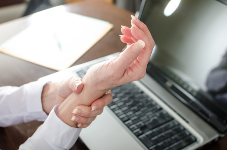 Businesswoman holding her painful wrist at office