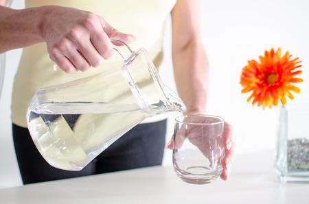 tomando agua: Verter el agua de una jarra en un vaso de mujer