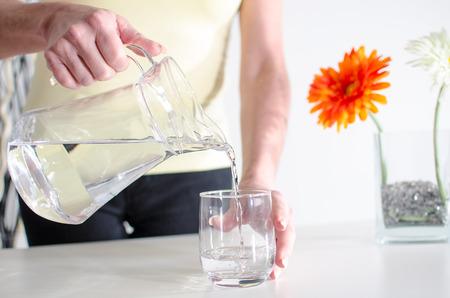 Vrouw gieten van water uit een kruik in een glas Stockfoto