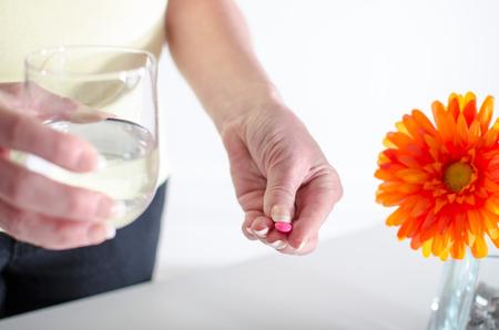 tomando refresco: Mujer a punto de tomar una pastilla con un vaso de agua