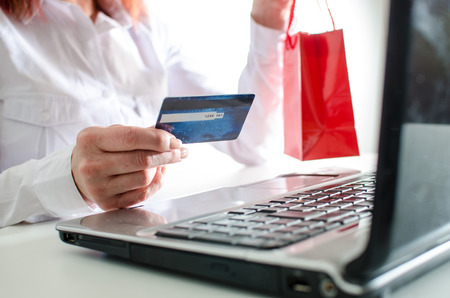 Woman with a shopping bag and a credit card being about to make a buying online