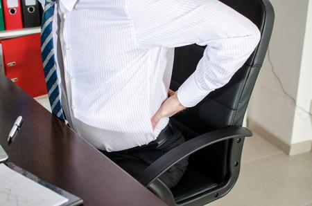 pain: Hombre de negocios con dolor de espalda en la oficina