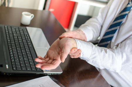 Businessman with wrist pain at office photo