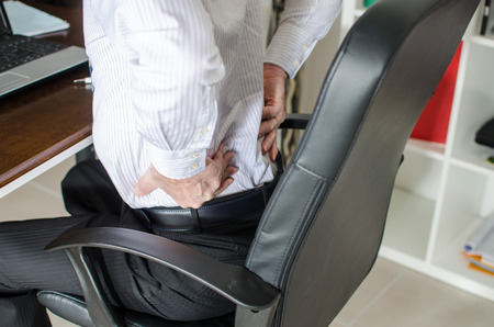 work injury: Businessman with back pain at office Stock Photo