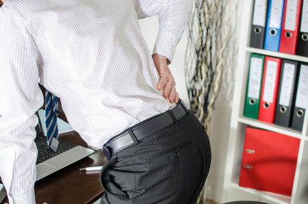 back injury: Businessman with back pain at office Stock Photo