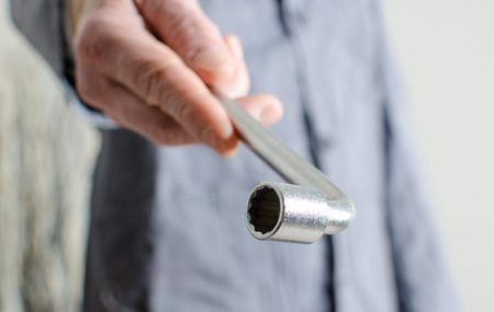 socket wrench: Hand holding a socket wrench, closeup