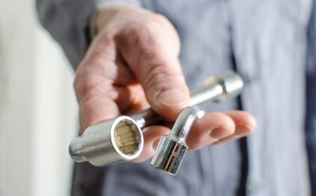 chrome man: Hand holding a two socket wrenches, closeup