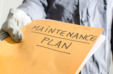 Worker holding a folder of maintenance plan, closeup