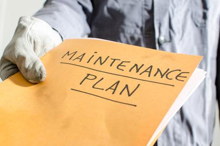 maintenance worker: Worker holding a folder of maintenance plan, closeup