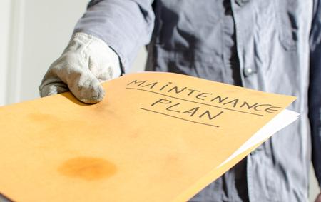 Worker holding a folder of maintenance plan, closeup